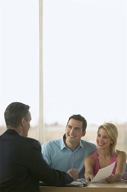 a smiling couple discusses funding with a man in a suit