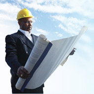 a man wearing a hard hat looks over blueprints