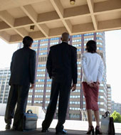 three office workers looking out the window at a high rise building