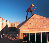 a worker on the roof of a house under construction