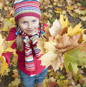 Fall scene. Girl playing in leaves