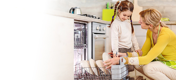 A woman and child filling a dishwasher