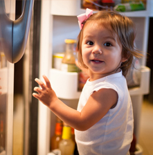Little girl standing in front of refrigerator