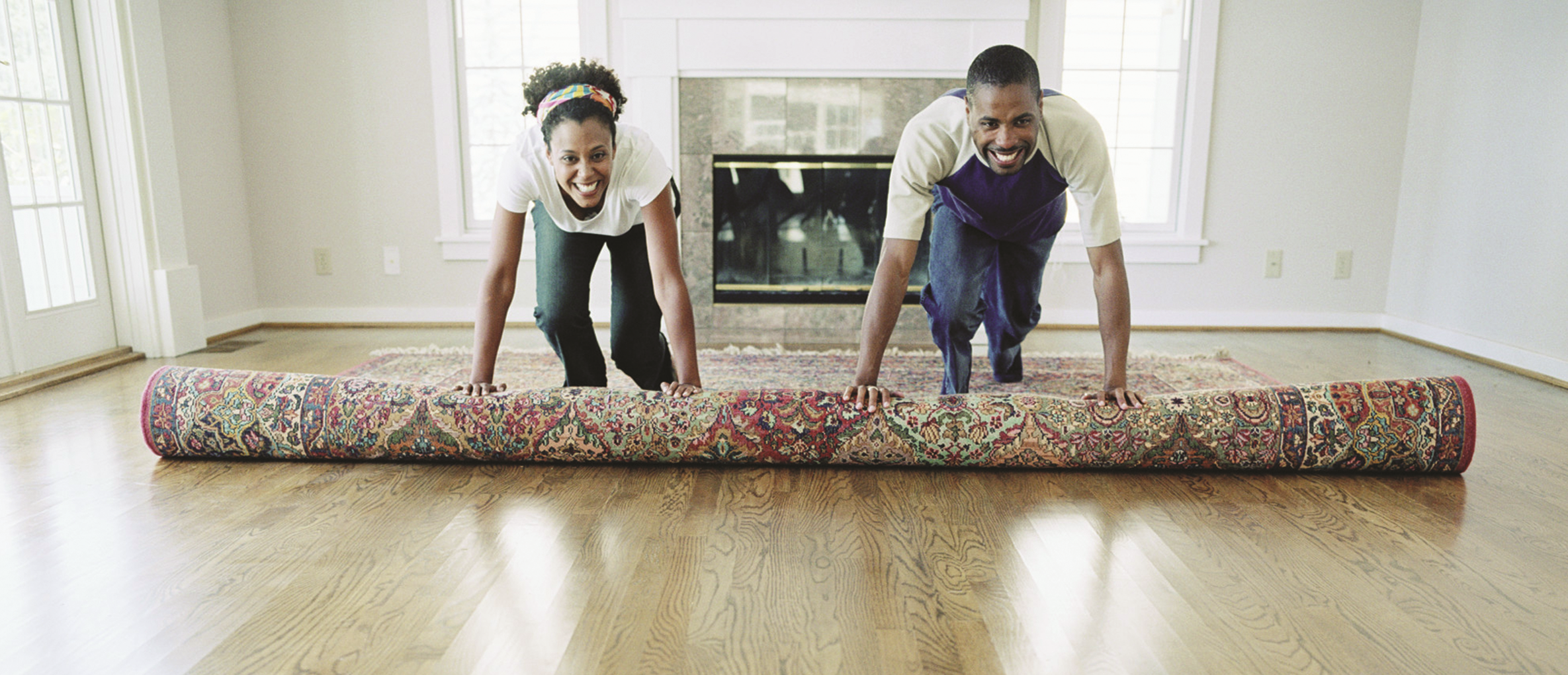 two people unrolling a carpet in a new home