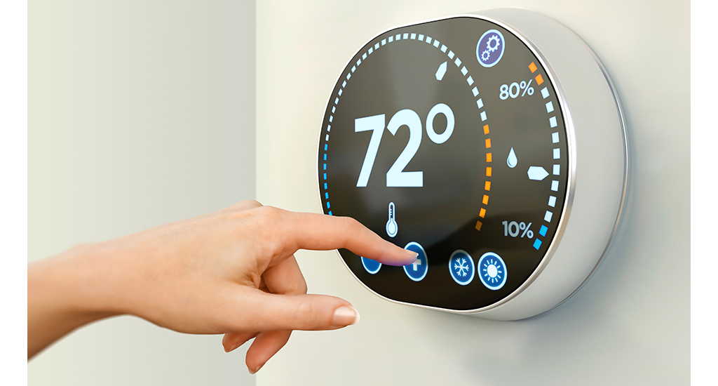 hand using smart thermostat
