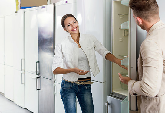 Woman and man shopping for a refrigerator in the store.