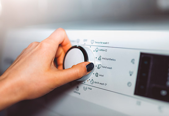 Woman adjusting the dial on a clothes washing machine.