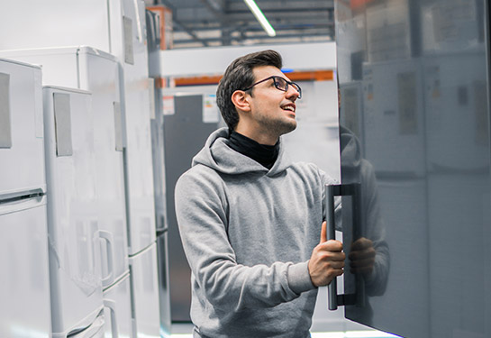 Man shopping for a refrigerator in the store.