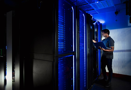 Man running tests on a server in a data center.