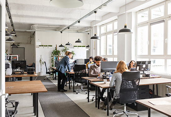 Open office space with people working at their stations.