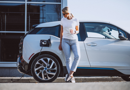 Woman leaning against a charging EV.