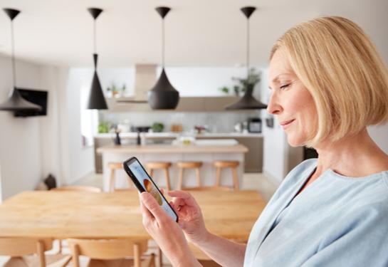 Woman looking at phone to set temperature.