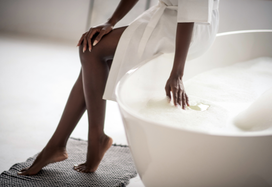Woman sitting on side of bathtub filled with water.