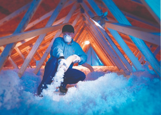 Contractor blowing insulation into attic.