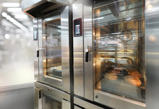 Commercial glass-door convection oven with bread baking inside.
