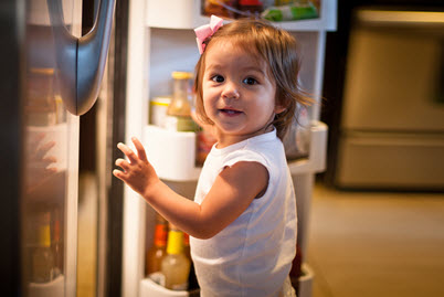 child standing in front of open refrigerator