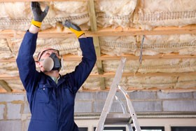 man adding insulation to ceiling