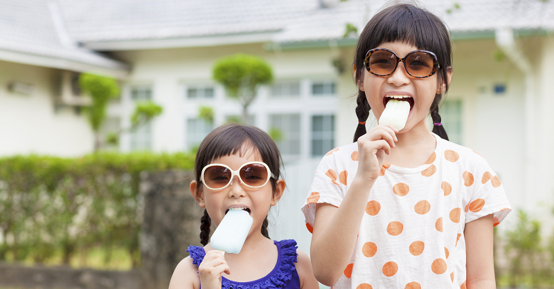Two girls eating popsicles outside.