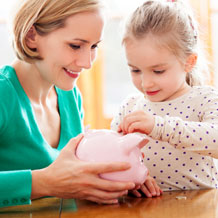 woman helping a child put money in a piggy bank