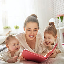 a woman reading to two children