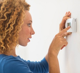 woman turning on a thermostat