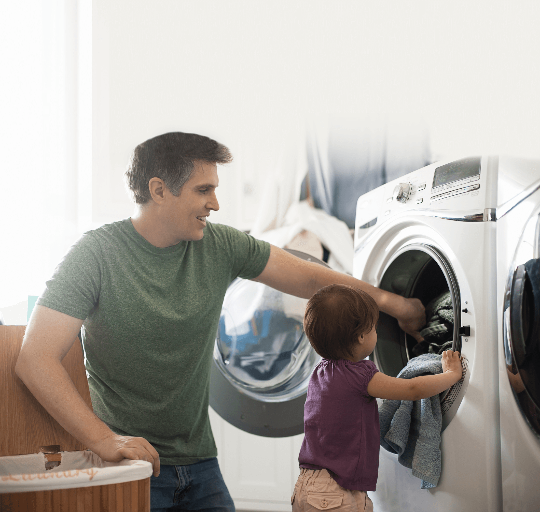 Father and Son putting laundry into clothes washer