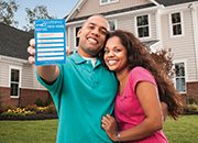 Man and woman, with the man holding the ENERGY STAR Certified Homes Label
