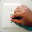 hand flipping a light switch