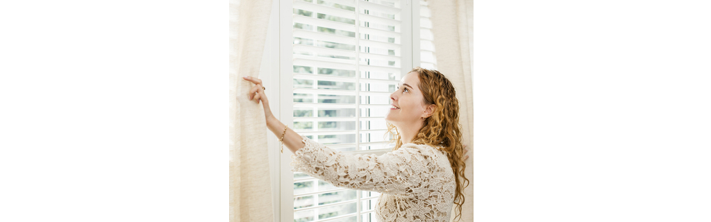 woman closing drapes