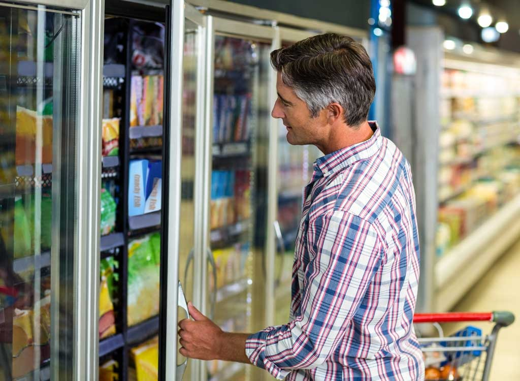 Man looking in grocery freezer