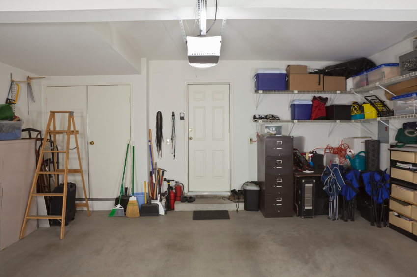 Wide angle view of a garage with the door leading into the house.