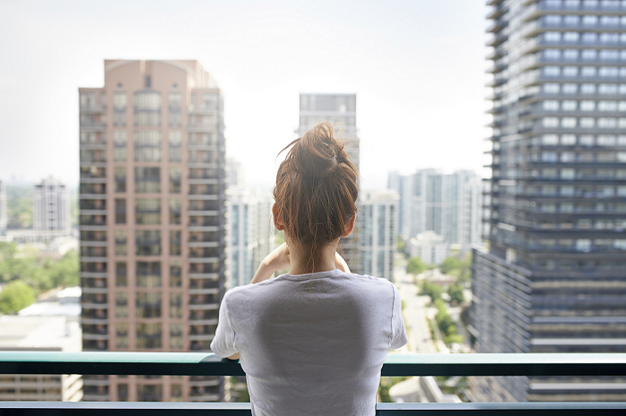 Woman looking out of her apartment