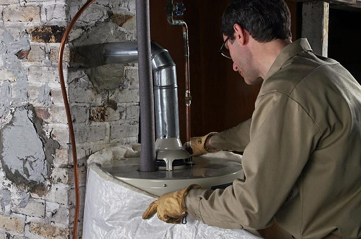 A man is wrapping a water heater in an insulating jacket.