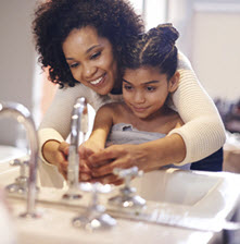 Woman and child washing their hands