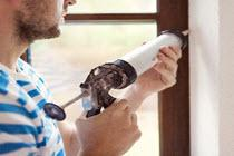 person caulking a window frame