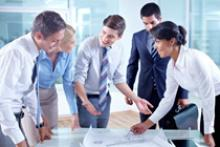 Photo of several people congregated around a building design plan.