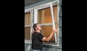 Man installing a storm window