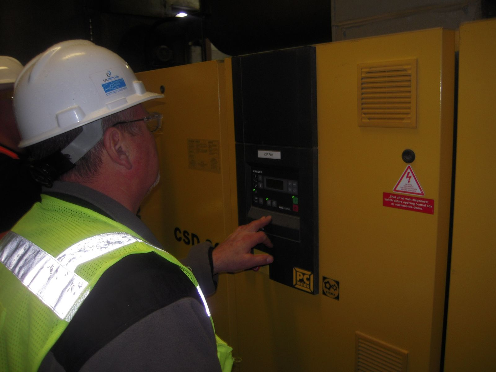 This photograph illustrates a worker taking an energy reading.